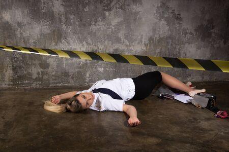 Imitación de la escena del crimen. Mujer policía muerta tirada en el suelo