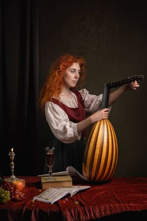 Red-haired girl in a historical suit plays the lute. Renaissance painting style. Stock Photo