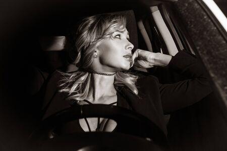Scene from a detective series. Killer strangles business woman in her car. Banco de Imagens