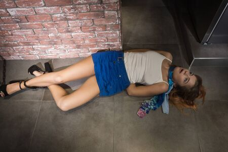 Crime scene simulation: dead girl in the handcuffs lying on the floor 版權商用圖片 - 131670411