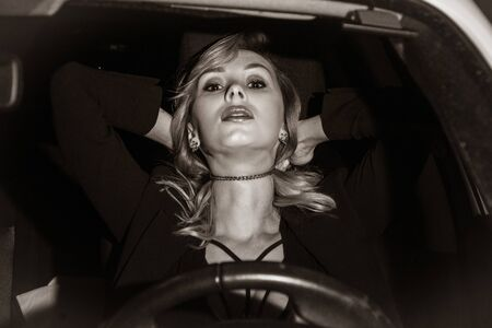 Scene from a detective series. Killer strangles business woman in her car. Stok Fotoğraf