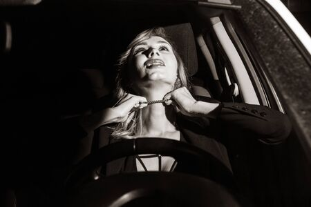 Scene from a detective series. Killer strangles business woman in her car.