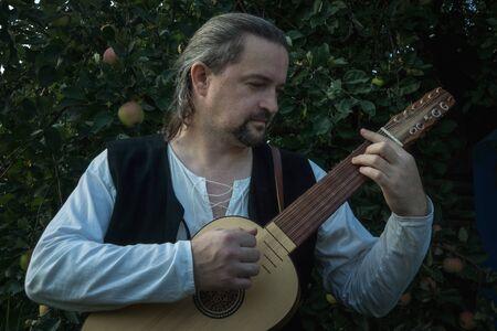 Adult man in historical suit playing vihuela in summer garden Reklamní fotografie