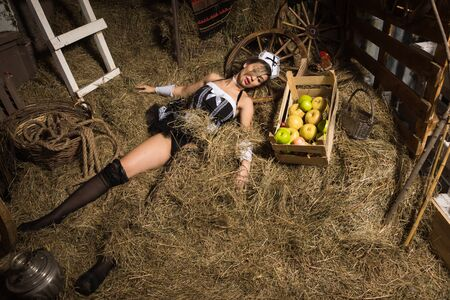 Crime scene imitation. Strangled chambermaid lying in the hay