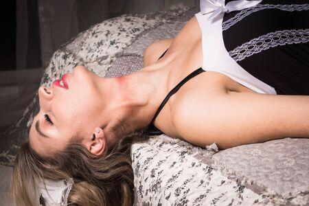 Crime scene imitation. Strangled chambermaid lying on the sofa Stock Photo