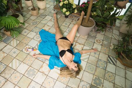 Body of a dead woman lying on the floor in the greenhouse Banque d'images