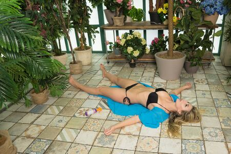 Body of a dead woman lying on the floor in the greenhouse Stock Photo