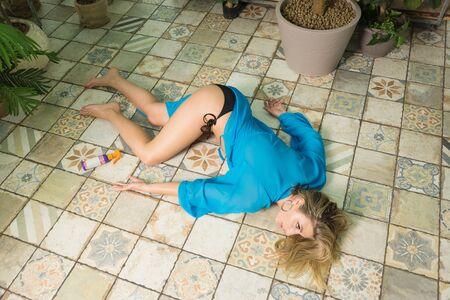 Leiche einer toten Frau, die im Gewächshaus auf dem Boden liegt