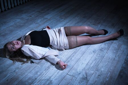 Crime scene with strangled pretty business woman lying on the floor