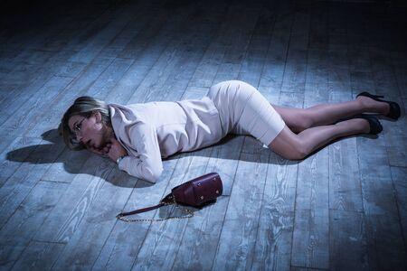 Crime scene with strangled pretty business woman lying on the floor Foto de archivo