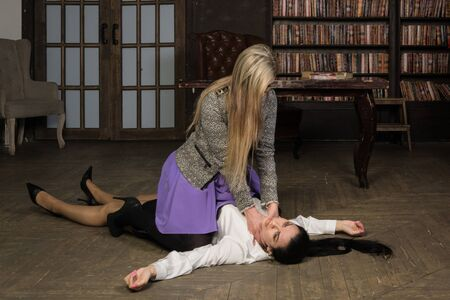 Deadly quarrel at office. One businesswoman strangles another Banque d'images