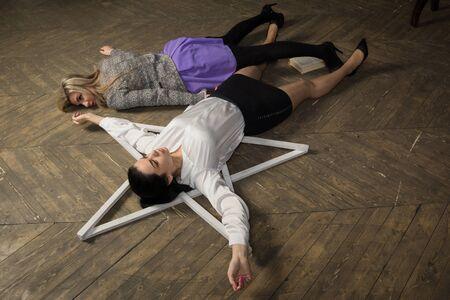 Triller film. Two women lie on the floor near the pentagram.