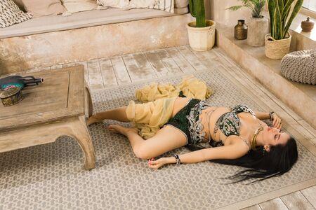 Crime scene imitation: lifeless woman in a traditional oriental costume lying on a floor Foto de archivo