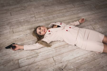 Crime scene (imitation). Pretty business woman lying on the floor. She shot in the chest.