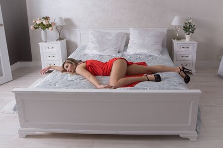 Strangled beautiful woman in a bedroom. Simulation of the crime scene.