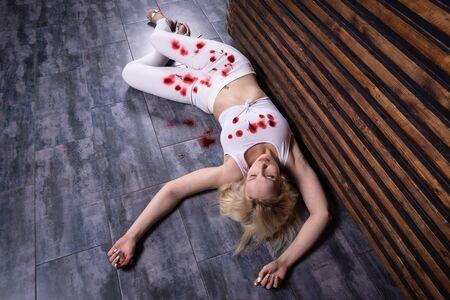 Crime scene (imitation). Pretty woman lying on the floor. She shot in the chest. Archivio Fotografico