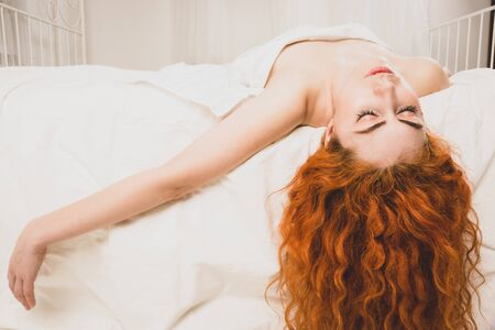 Beautiful redhaired woman lying on bed in bedroom.