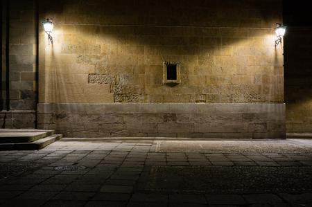 Wall illuminated by lampposts, during the night, in the old town of Salamanca, Spain Stock Photo