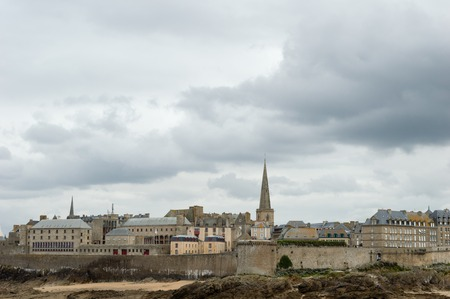 View of the walled city of Saint Malo, with the steeple of the cathedral protruding above the buildings behind the wall, city of Privateers - in Brittany, France, in a cloudy day of autumn