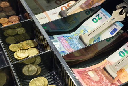 Vue grand angle du tiroir-caisse rempli de pièces de monnaie et de billets en euros
