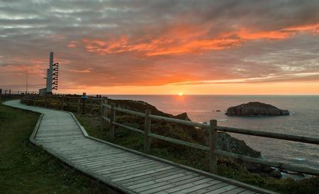 Foghorn and wooden walkway near lighthouse Peñas Cape on a beautiful sunset Coast of Asturias, Spain