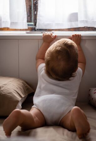 Happy baby sitting on bed playing and looking in window at home 写真素材 - 131697163