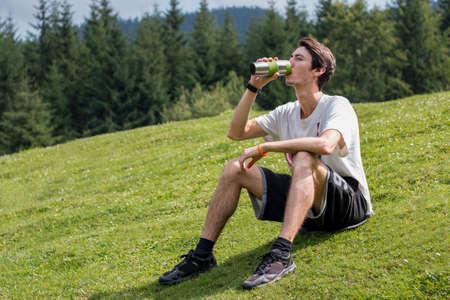 man drinking water: man drinking water on a green meadow