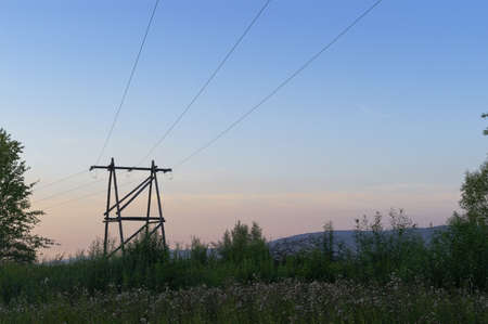 Overhead power line with a wooden pylons on sunset sky background