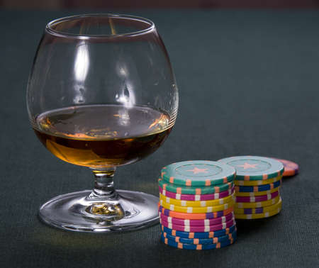 Glass with cognac and chips for a game in a casino photo