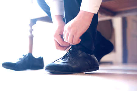 The groom puts on, ties laces on footwear photo