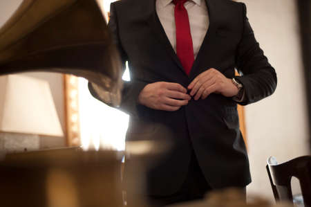 wrist cuffs: The groom,  man clasps a button at a jacket Stock Photo