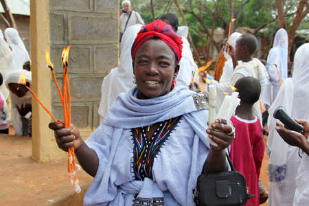 amharic: TURMI, ETHIOPIA - NOVEMBER 22, 2011: The woman prays with the burning candles in hands during celebration in orthodox church. November 22, 2011 in Turmi, Ethiopia.