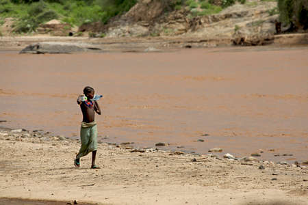 ethnology: SOUTH OMO - ETHIOPIA - November 24, 2011: Unidentified african girl goes on the river bank and bears bottles with water on November 24, 2014 in South Omo, Ethiopia.