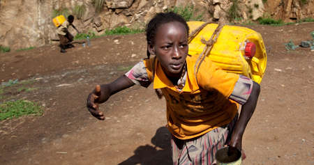 rift: SOUTH OMO - ETHIOPIA - NOVEMBER 19, 2011: Unidentified girl bears the canister with water, in November 19, 2011 in Omo Rift Valley, Ethiopia.
