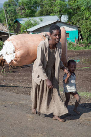 SOUTH OMO - ETHIOPIA - NOVEMBER 19, 2011: The woman with the son come back from work on a cotton plantation, Africa., in November 19, 2011 in Omo Rift Valley, Ethiopia.