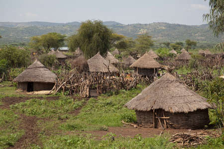 View of an African village with small huts 免版税图像