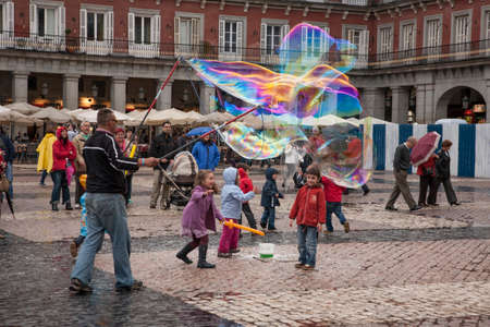 MADRID, SPAIN - APRIL 22, 2011: Unidentified street artist blows huge colorful soap bubbles in Plaza Mayor, Madrid on April 22, 2011 in Madrid, Spain.
