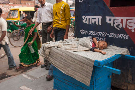 beggary: NEW DELHI, INDIA - OCTODER 29,2006: A little Indian boy sleeping on the street of New Delhi, India.