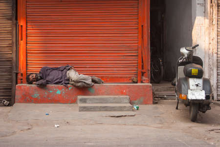 squalor: NEW DELHI, INDIA - October 30, 2006: Unidentified Indian homeless man sleeps on the streets of New Delhi, India.