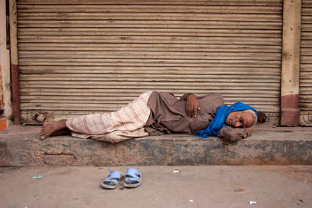 impoverished: NEW DELHI, INDIA - October 30, 2006: Unidentified Indian homeless man sleeps on the streets of New Delhi, India.