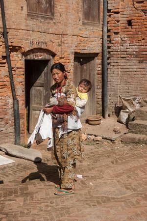 KATHMANDU, NEPAL - NOVEMBER 06, 2006: The woman with child on the street of Katmandu, Nepal.