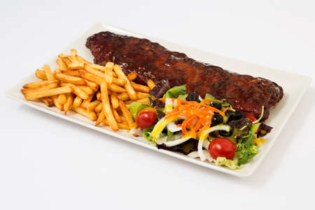 Baked pork ribs with barbecue or BBQ sauce. Фото со стока