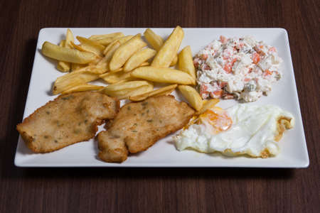 Closeup of a combo platter with fried egg, fish, french fries and russian salad