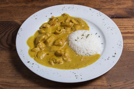 Chicken dansak curry with pilau rice and fork on a white plate