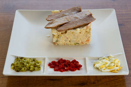 Salad with tuna, vegetables and eggs on a white plate with eggs and chicks.