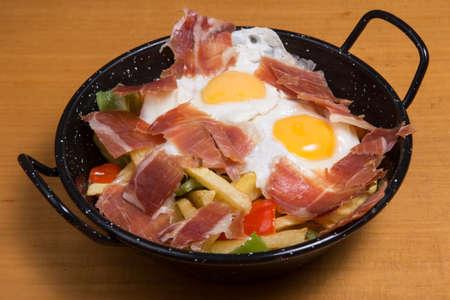 Tapas huevos rotos broken eggs with ham and yolk from Spain