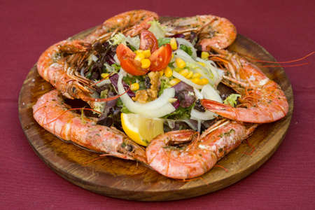 Fried or Roasted tiger big shrimps in plate with salad and lemon. Grilled seafood. Healthy food. Prawns Scampi traditional dish. Appetizer langoustines.