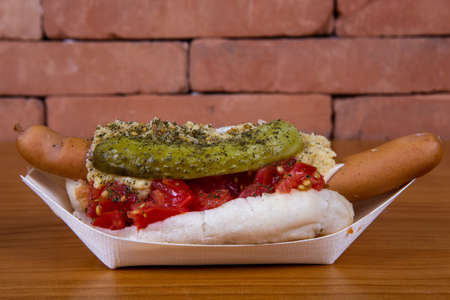 One Hot Dog with mustard, pickled cucumber, onion on a light wood background. Fast food, street meal.