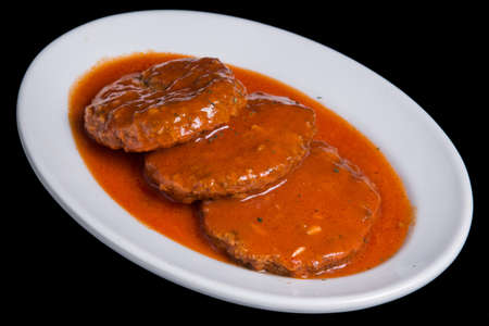 Meat cutlets in tomato sauce, baked in a frying pan.
