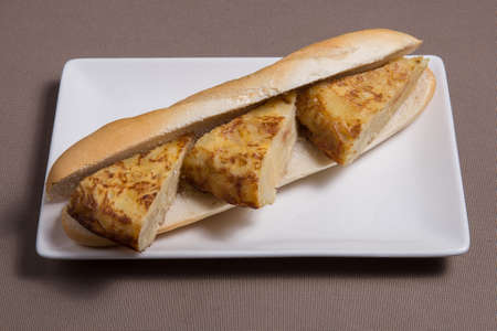 Sandwich with tortilla de patata on a white plate. Spanish tapas.